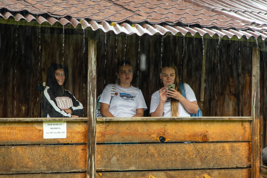 люди прячутся от дождя на веранде