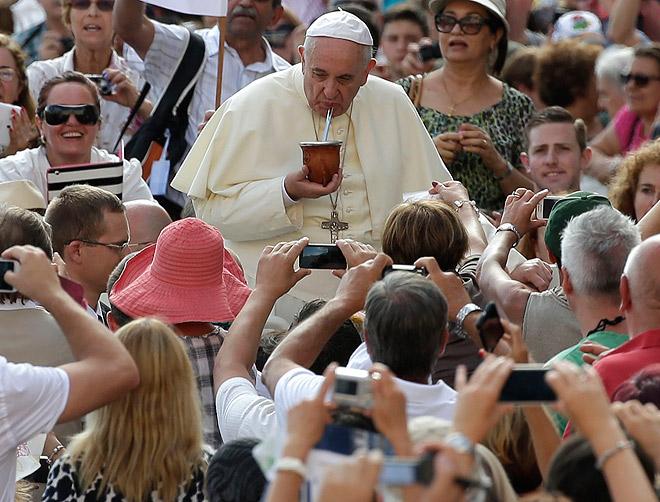 """Папа Римский Франциск I пьёт предложенный кем-то из прихожан популярный южноамериканский напиток """"мате"""" по пути на мессу в Ватикане."""
