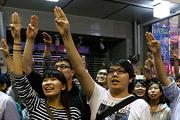 """Сторонники реформ в Гонконге выстроились для фотографии, демонстрируя жест из популярного голливудского фильма """"Голодные игры""""."""