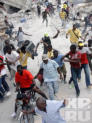 Местный полицейский разгоняет толпу мародеров железным прутом