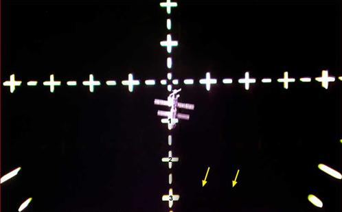 """МКС, снятое сквозь оптический прицел """"Атлантиса"""". Стрелками обозначены сомнительные звезды"""