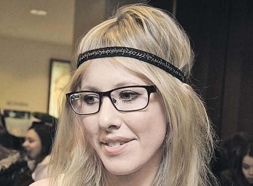 На Ксении очки прямоугольной формы, достаточно вытянутые...