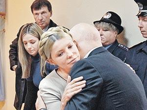 Последние объятия перед 7-летним расставанием. Юлию Тимошенко успокаивает ее муж Александр, за спиной у нее - дочь Евгения