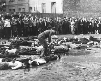 Литва, Каунас, 27 июня 1941 года. Пособник нацистов из числа местных жителей добивает железным прутом евреев, казненных на городской площади.