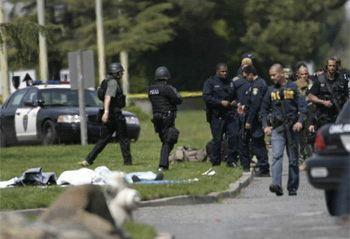 На газоне лежит одна из жертв расстрела,  вынесенная из здания университета.  Многочисленные полицейские прибыли уже к развязке трагедии