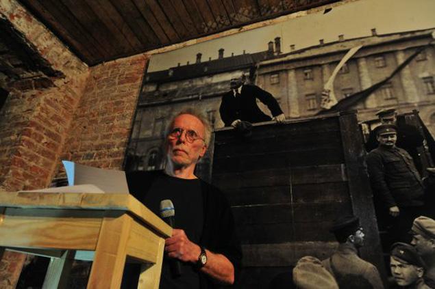 Фотограф-коллекционер Дэвид Кинг на фоне знаменитой фотографии 1920 года. Ленин - на трибуне, на ступеньках - Троцкий, за ним - Каменев. Потом Троцкого и Каменева заретушировали.