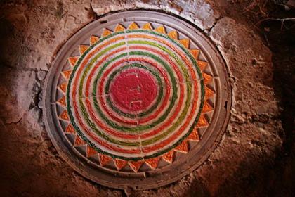 Канализационные люки, расписанные  под древние монеты