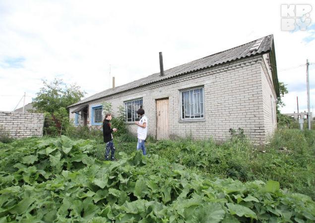 Сирота показывает место у входной двери дома, где раньше готовила еду на костре