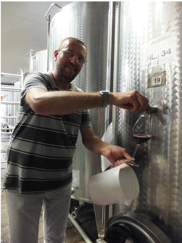 Винодел Роберто наливает санджовезе, которое только-только готовятся разливать по бутылкам.