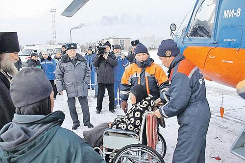 Колясочницу Серафиму спасатели вывозят из тайги.