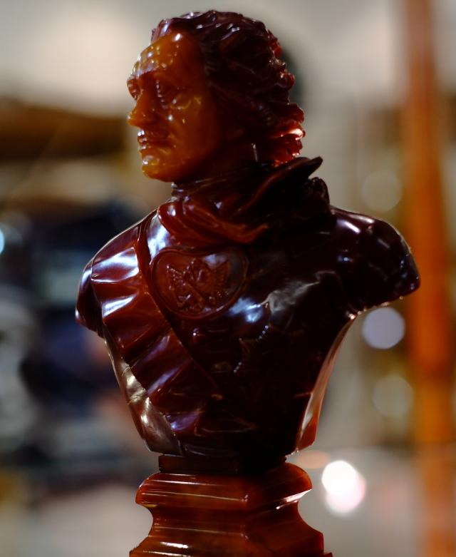 Бюст Петра Первого выполнен из древнего куска янтаря темно-оранжевого цвета.