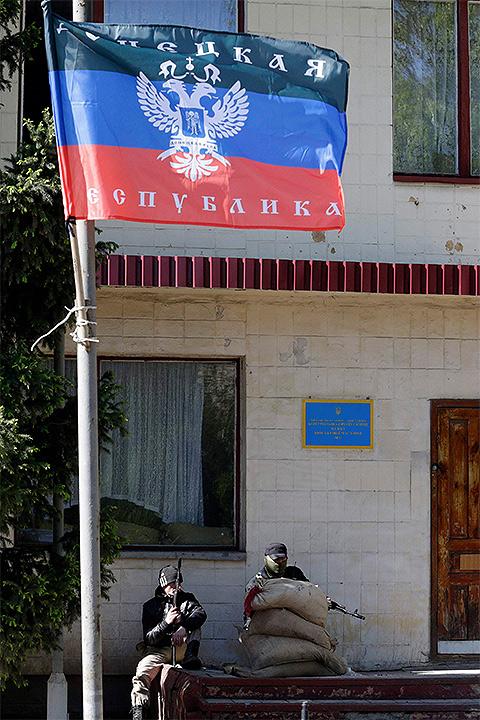 Вооруженные сторонники Донбасской народной республики у входа в административное здание в центре столицы региона