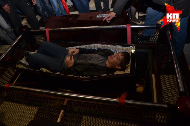 Всем желающим предлагается лечь в гроб, который закрывают крышкой и спускают на лентах в могилу.