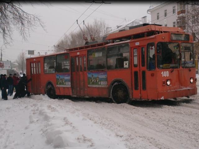 Пассажири толкают, застрявший в снегу, общественный транспорт